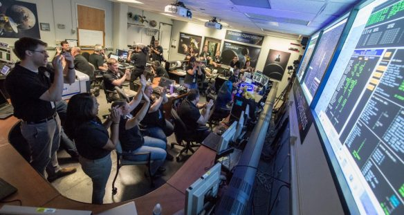 New Horizons Flight Controllers celebrate after they received confirmation from the spacecraft that it had successfully completed the flyby of Pluto, Tuesday, July 14, 2015 in the Mission Operations Center (MOC) of the Johns Hopkins University Applied Physics Laboratory (APL), Laurel, Maryland. Photo Credit: (NASA/Bill Ingalls)